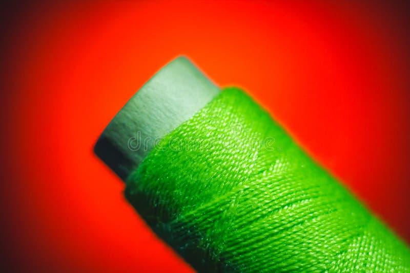 Plan rapproché vert de fil de couture sur le fond rouge image libre de droits