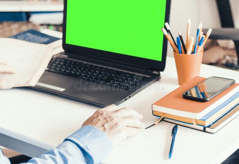 Plan rapproch? d'homme de main utilisant une souris et de la dactylographie sur l'ordinateur portable vert d'?cran sur la table b photo stock