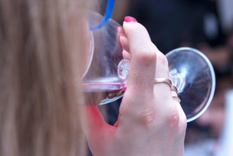 Plan rapproch? de belles languettes femelles buvant du vin photographie stock
