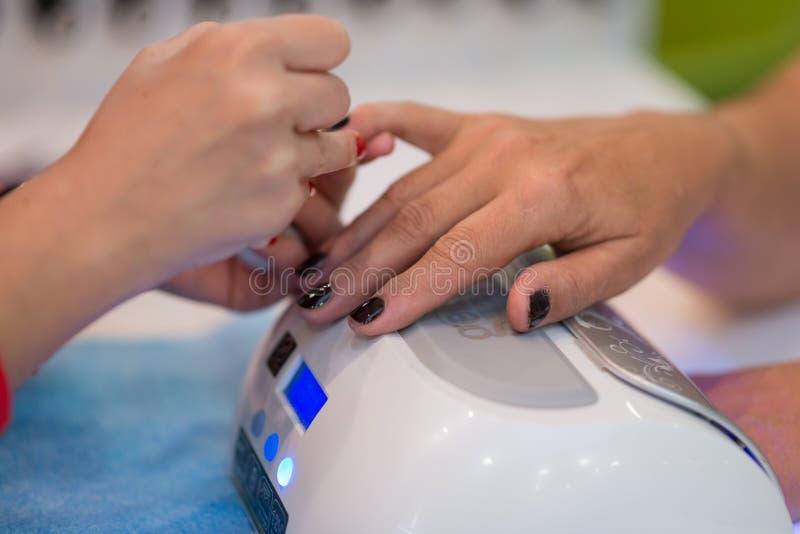 Plan rapproch? de belles mains de femme obtenant la manucure dans le salon de station thermale images stock