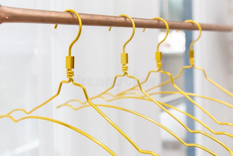 Plan rapproch? de cintre d'or en m?tal sur la corde ? linge de cuivre avec le fond blanc de rideau images libres de droits