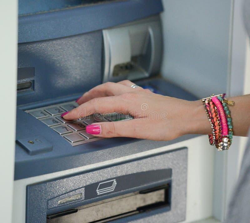 Plan rapproch? de main ?crivant le code de PIN/pass sur le clavier num?rique de machine d'ATM/bank images stock