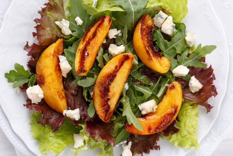 Plan rapproch? de salade mixte fra?che Feuilles de laitue et d'arugula avec la p?che et le fromage bleu grill?s photos stock