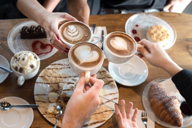 Plan rapproch? des mains avec des tasses de caf? dans un caf? photographie stock libre de droits