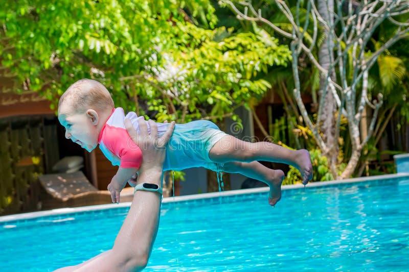 Plan rapproch? Distribue de l'eau en laquelle un petit enfant a l'amusement Vacances d'?t? dans la piscine Vieux rires de huit mo photos stock