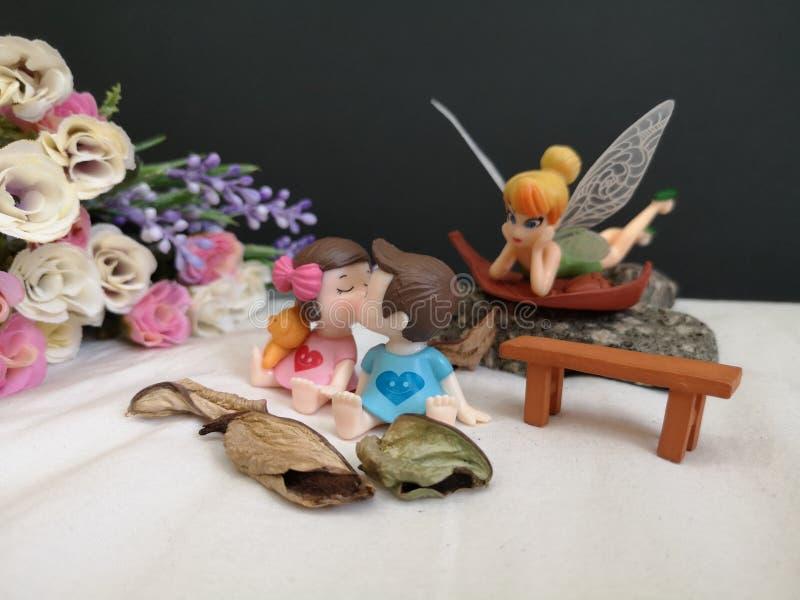 Plan rapproch? et macro tir des b?b?s de baiser miniatures dans le jardin tandis que f?e Tinkerbell ?grappant derri?re images stock
