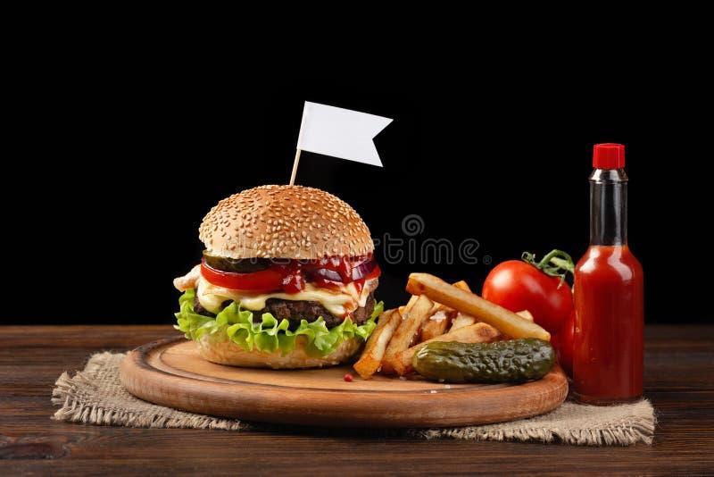 Plan rapproch? fait maison d'hamburger avec du boeuf, la tomate, la laitue, le fromage et les pommes frites sur la planche ? d?co photos libres de droits