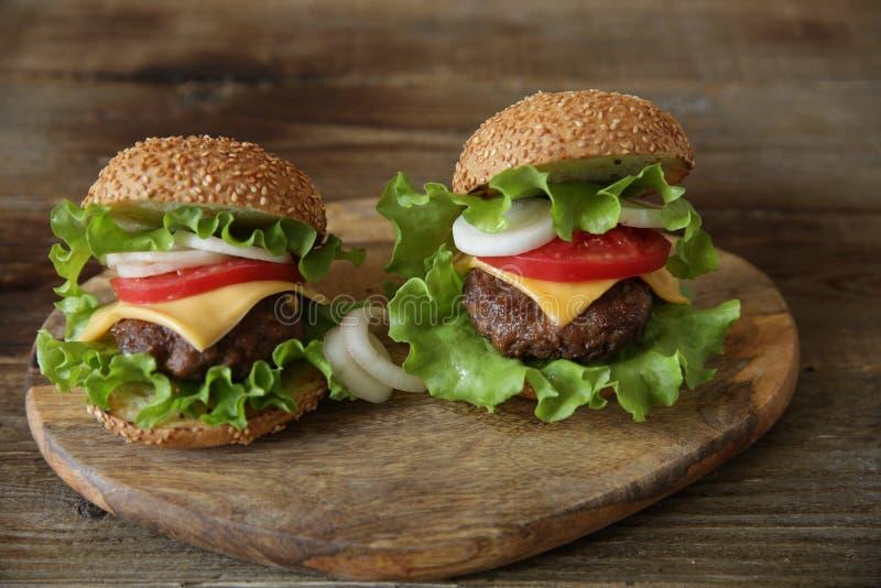Plan rapproch? Hamburger deux avec la côtelette de boeuf, avec du fromage, conserves au vinaigre, tomates, oignons, laitue sur un images libres de droits