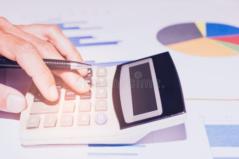 Plan rapproch? Main de calculatrice fonctionnante d'affaires ou de compte, b?n?fice ou ?conomie de graphique sur le si?ge social photo stock
