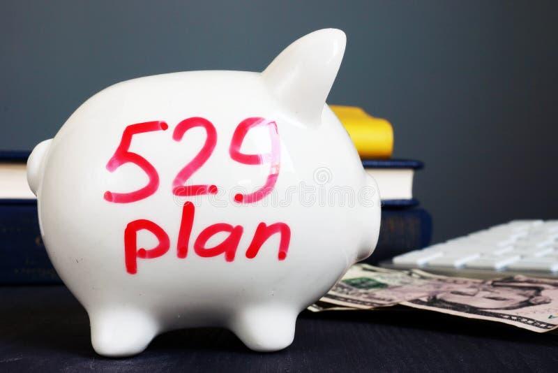 plan som 529 är skriftligt på en spargris Högskolabesparingplan royaltyfri bild