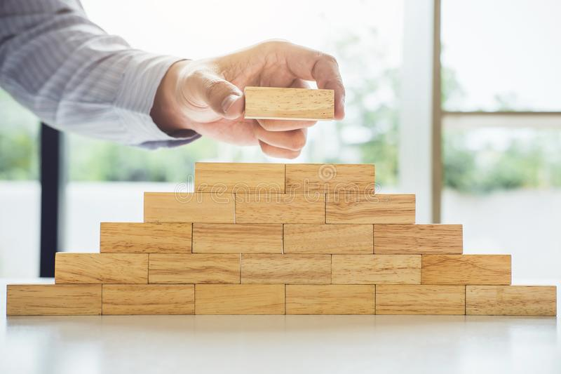 Plan and strategy in business, Risk To Make Business Growth Concept With Wooden Blocks, hand of man has piling up and stacking royalty free stock photo