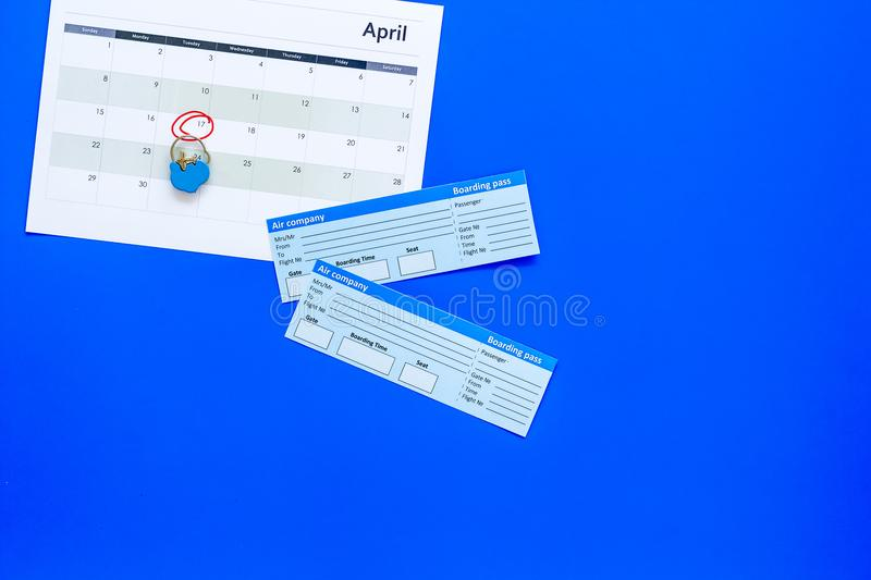 Plan a trip. Buy airplane tickets. Tickets near calendar with date circled on blue background top view copy space. Plan a trip. Buy airplane tickets. Tickets stock photo