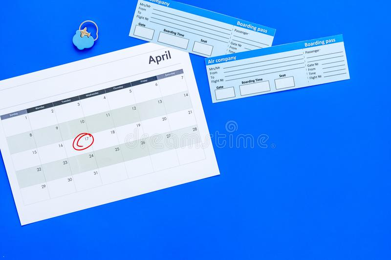 Plan a trip. Buy airplane tickets. Tickets near calendar with date circled on blue background top view copy space. Plan a trip. Buy airplane tickets. Tickets royalty free stock photos