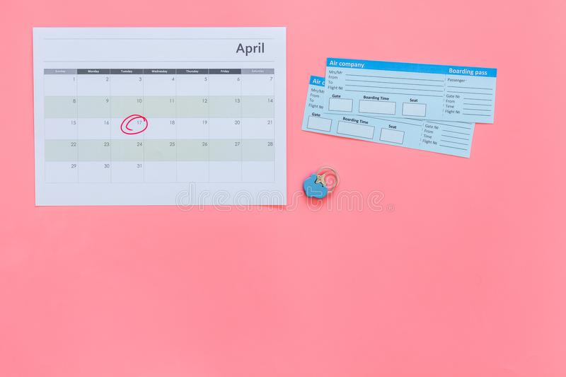 Plan a trip. Buy airplane tickets. Tickets near calendar with date circled on pink background top view copy space. Plan a trip. Buy airplane tickets. Tickets royalty free stock image