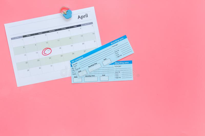 Plan a trip. Buy airplane tickets. Tickets near calendar with date circled on pink background top view copy space. Plan a trip. Buy airplane tickets. Tickets royalty free stock photography