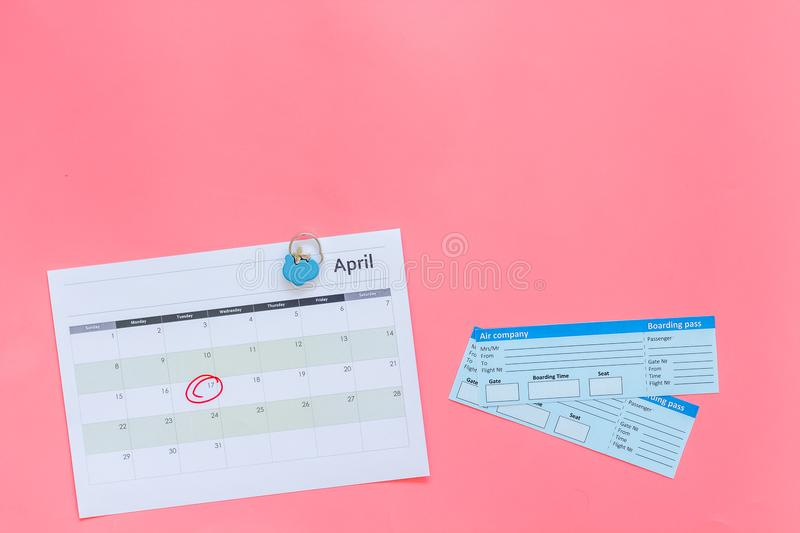 Plan a trip. Buy airplane tickets. Tickets near calendar with date circled on pink background top view copy space. Plan a trip. Buy airplane tickets. Tickets stock images