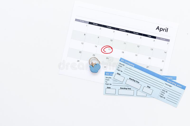 Plan a trip. Buy airplane tickets. Tickets near calendar with date circled on white background top view copy space. Plan a trip. Buy airplane tickets. Tickets royalty free stock images