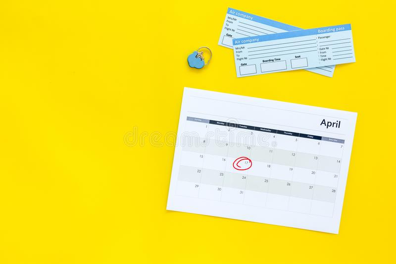 Plan a trip. Buy airplane tickets. Tickets near calendar with date circled on yellow background top view copy space. Plan a trip. Buy airplane tickets. Tickets royalty free stock photography