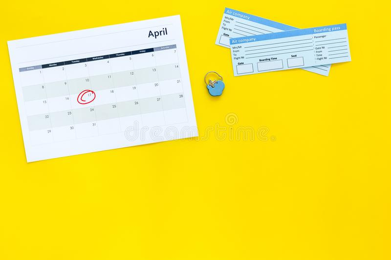 Plan a trip. Buy airplane tickets. Tickets near calendar with date circled on yellow background top view copy space. Plan a trip. Buy airplane tickets. Tickets stock image
