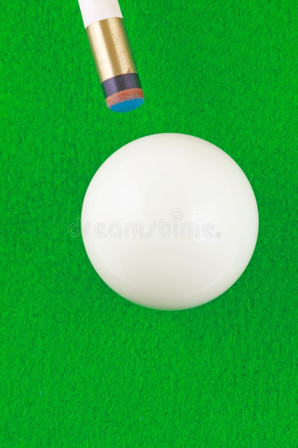 Cue and ball. A plan view of a white ball being cued on a green beize background stock photography