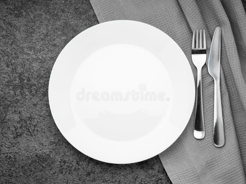 Plan vit platta för mellanrum, gaffel på mörker - grå stenbetongtabell, bästa sikt Åtlöje upp, kopieringsutrymme royaltyfria bilder