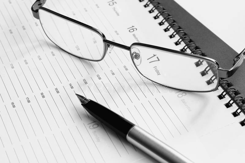 Plan for the week. Glasses in a metal frame and pen with an open gold pen on the organizer. Black and white photography. Business. Black and white photography royalty free stock photo