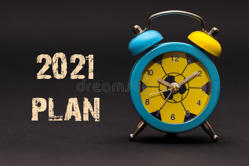 2021 plan written with alarm clock on black paper background stock photography