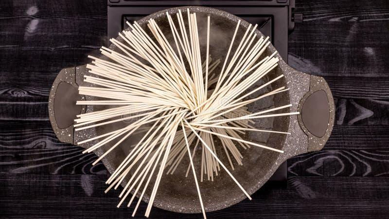 Plana nudlar kokade i koka vatten i en kastrull med en stenbel royaltyfri fotografi