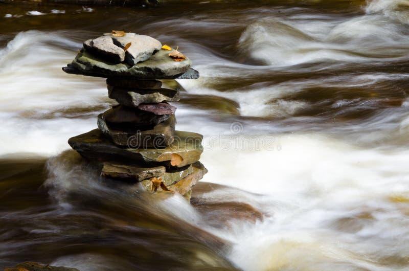 Plana Rocks som staplas i en flod royaltyfri foto