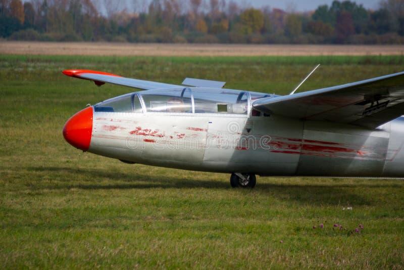Planador velho na grama da pista de decolagem fotografia de stock royalty free