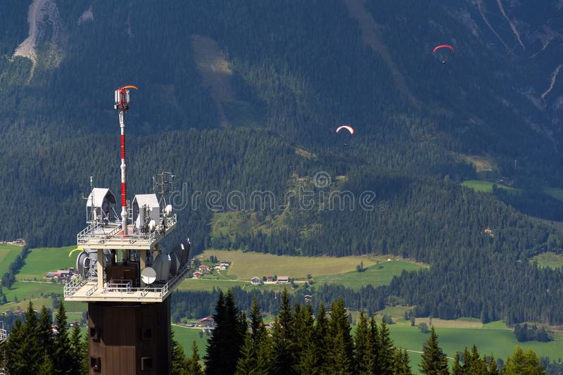 Planai telecommunication tower with flying paragliders in background. Schladming, Austria royalty free stock images