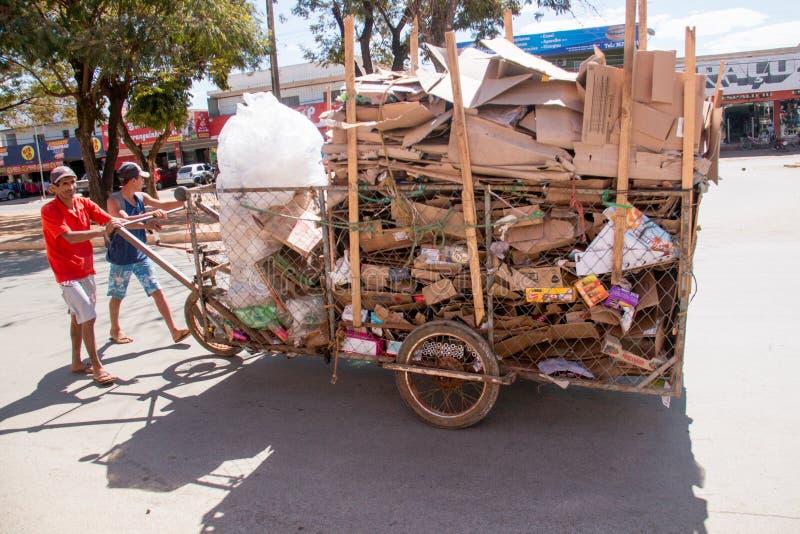 Planaltina, Goa-¡ s, Brasilien 27. Juli 2019: Zwei Männer, die Pappe für die Wiederverwertung in einem selbst gemachten Wagen sam stockfotos
