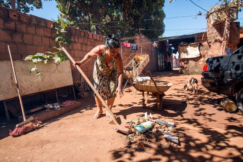 Planaltina, Goa ¡ s, 7 Brazilië-Juli, 2018: Een vrouw die haar binnenplaats schoonmaken royalty-vrije stock fotografie