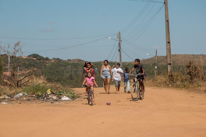 Planaltina, Goiás, Brasil 6 de julho de 2019: Uma família que anda abaixo de uma rua da sujeira imagem de stock royalty free