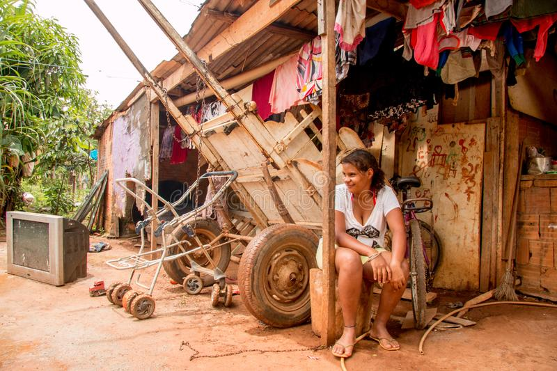 Planaltina, Goiás, Brazil-December 8, 2018: A poor girl sitting out in front of her home. In the poor community of Planaltina stock photos