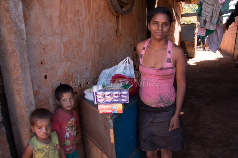 Planaltina, Goiás, Brazil-July 7, 2018: A mother with two of her children standing next to some food stock photo