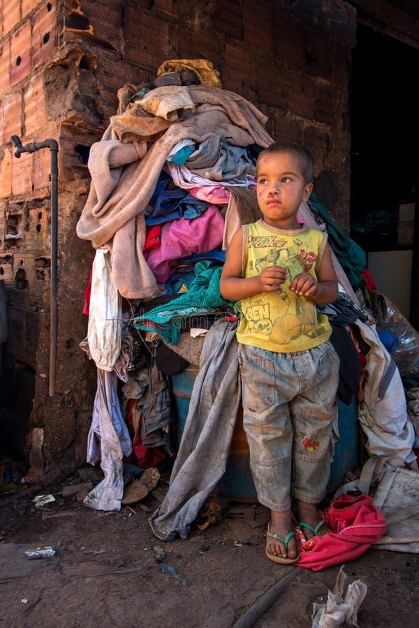 Planaltina, Goias, Brasil 7 de julho de 2018: Uma posição do rapaz pequeno na frente de uma pilha grande da lavanderia imagens de stock