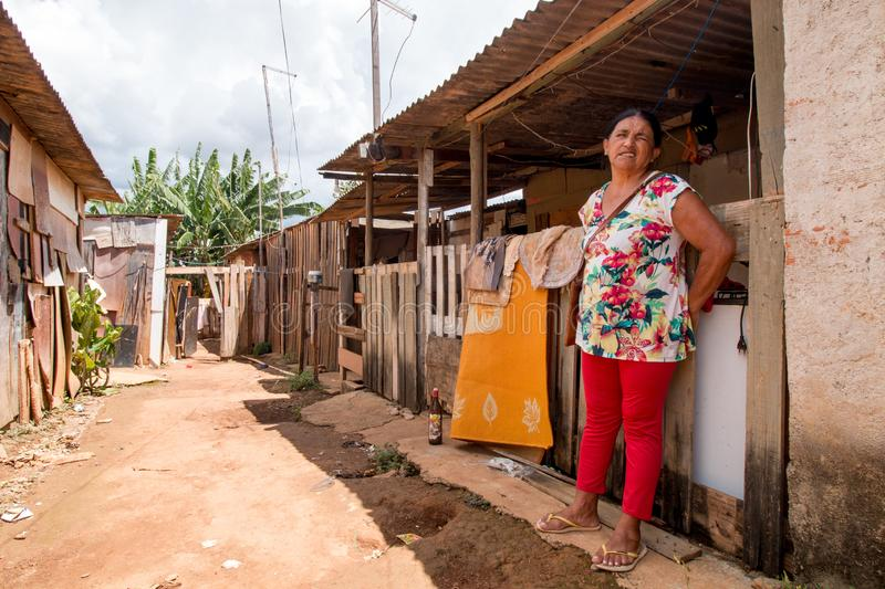 Planaltina, Goias, Brazil-August 23, 2019: A poor woman stands in front of her home. That is illegally built, known as an invasion in the poor impoverish city stock photos