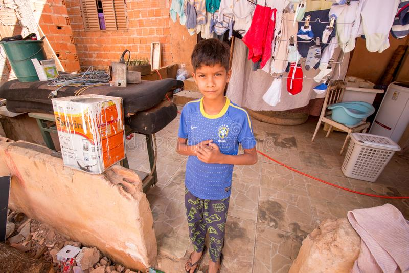Planaltina, Goias, Brazil-July 27, 2019: A poor boy standing in the back of his home. Planaltina, Go¡as, Brazil-December 8, 2018: A poor boy standing outside stock photo