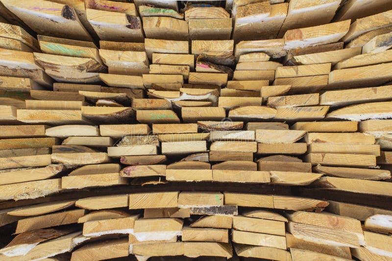 Plance marroni e grige di legno piegate in una segheria Bordi accatastati dell'ontano come struttura immagini stock