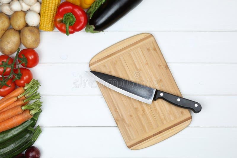 Planche à découper à cuire végétarienne en bonne santé avec le couteau et le vegetabl images libres de droits