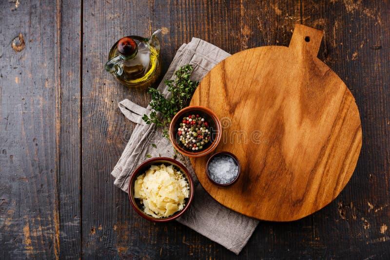 Planche à découper, assaisonnements et parmesan image stock