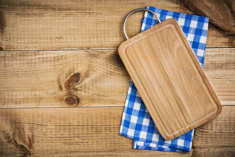 Planche à découper au-dessus de serviette de cuisine bleue sur le fond en bois de texture image libre de droits