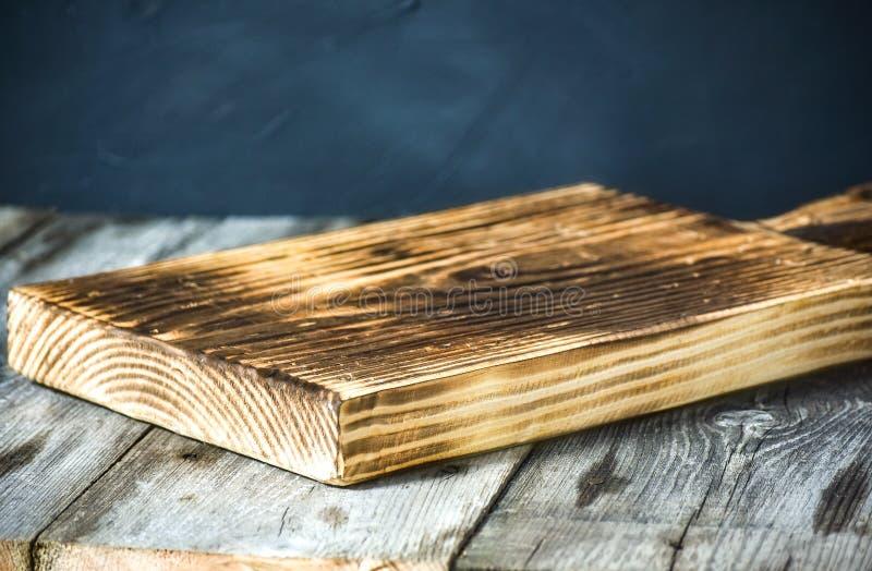 Planche à découper au-dessus de serviette sur la table de cuisine en bois photographie stock