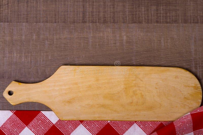 Planche à découper au-dessus de serviette sur la table de cuisine en bois images stock