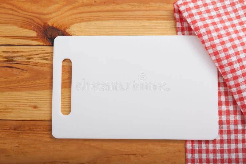 Planche à découper au-dessus de serviette sur la table de cuisine en bois Vue supérieure images libres de droits
