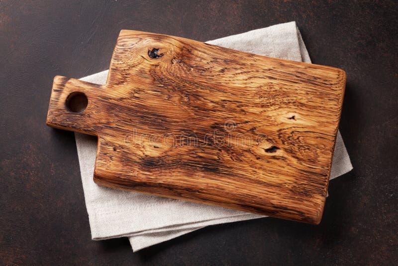 Planche à découper au-dessus de serviette sur la table de cuisine en pierre photos libres de droits