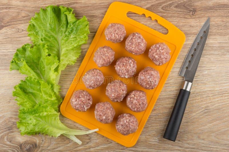 Planche à découper avec les boulettes de viande crues, les feuilles de la laitue et le couteau photo stock