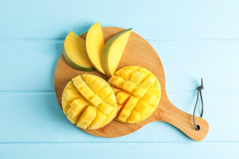 Planche à découper avec les mangues mûres coupées sur le fond de couleur photos stock