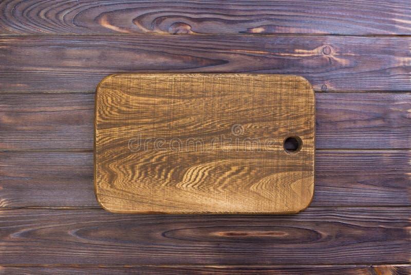 Planche à découper de vintage avec l'espace pour le texte sur le vieux fond en bois, plan rapproché image libre de droits